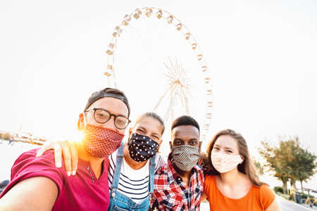 Photo pour Multiracial milenial students taking selfie protected by face masks - New normal travel concept with young people having safe fun together at ferris wheel - Bright sunshine filter with tilted angle - image libre de droit
