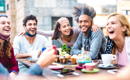Photo for Multiracial friends having fun drinking together at coffee house - Young people laughing at restaurant cafeteria - New normal lifestyle concept with happy guys and girls at cafe bar - Bright filter - Royalty Free Image