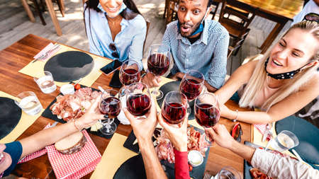 Photo pour Friends drinking red wine at restaurant bar wearing open face mask - New normal lifestyle concept with happy people having fun together toasting at tavern bar - Warm vivid filter with focus on glasses - image libre de droit