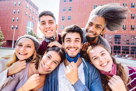 Photo for Multiracial friends taking selfie with opened face mask at college campus - Happy friendship concept with young students having fun together after university reopening - Bright backlight filter - Royalty Free Image
