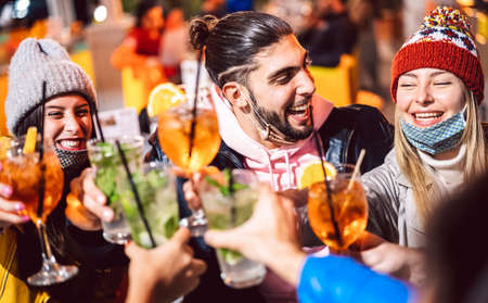 Photo pour Happy friend toasting fancy drinks at night bar with open mask - New normal lifestyle concept with milenial people having fun together on winter clothes at apreski - Focus on guy face - image libre de droit