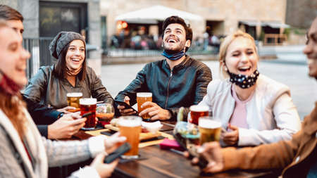 Photo pour Young friends drinking beer wearing face mask - New normal lifestyle concept with people having fun together talking on happy hour at outside brewery bar - Bright warm filter with focus on central guy - image libre de droit