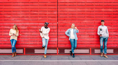 Photo for Multicultural friends group using smartphone by red wooden background - Technology and urban lifestyle concept with millenial people sharing content online with modern mobile phones - Vivid filter - Royalty Free Image