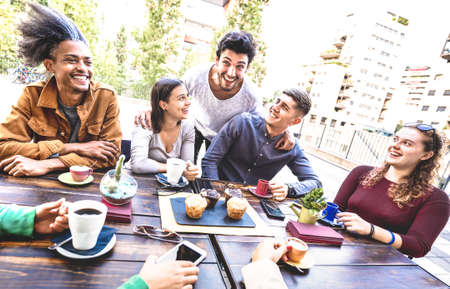 Photo pour People group drinking cappuccino at coffee bar restaurant - Friends talking and having fun together at outdoors cafeteria - Life style concept with happy men and women at cafe - Warm bright filter - image libre de droit