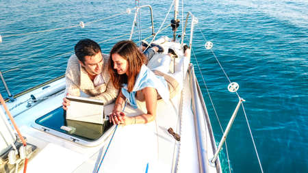 Photo for Young couple in love having fun with tablet pc on sailboat - Royalty Free Image
