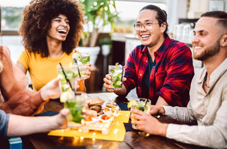 Photo for Young friends toasting mojito drinks at fashion cocktail pub restaurant - Life style concept with milenial people having drunk fun cheering on happy hour at bar - Royalty Free Image