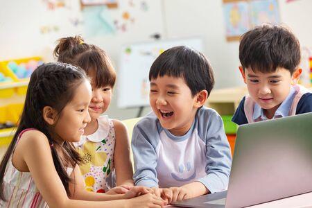 Photo pour The kindergarten children watch video - image libre de droit