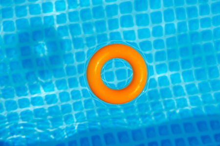 Photo pour orange Inflatable ring floating in swimming pool on sunny day, top view - image libre de droit