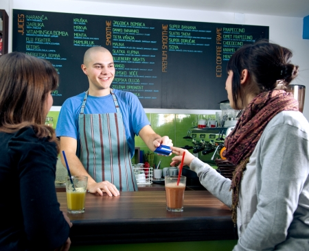 Bertender receiving credit card of customer for payment in cafe