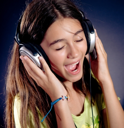 Cute girl with headphones singing.  Dark background.