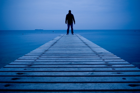 Man standing on a wooden pier in the dusk
