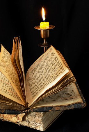 old religious book and candle on black background,