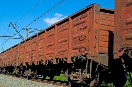 Rusty brown freight cars passing over a grade crossing against blue sky