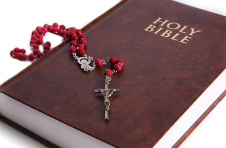 The Holy Bible displayed with a red rosary on it. Focus is on the cross of the rosary. Perfect for easter or christmas theme.