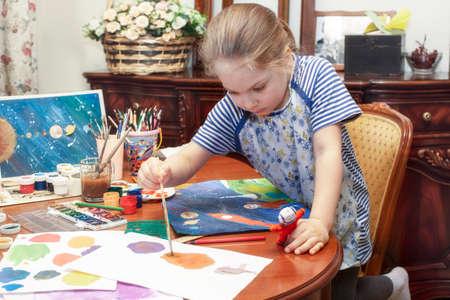 Foto de A child paints a papier mache astronaut figurine with a brush - Imagen libre de derechos