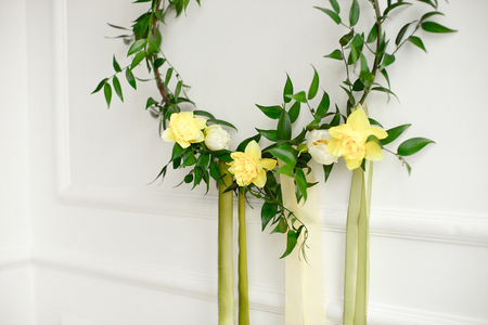 Close-up green wreath of narcissus and plants on the white wall.