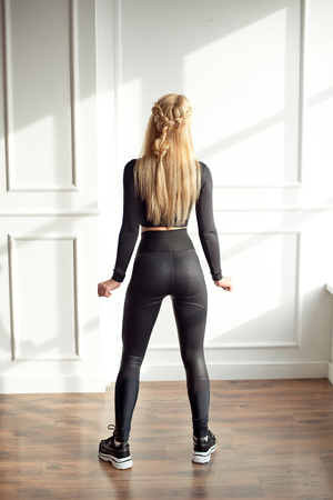 Photo for Young slim woman with an athletic body blonde hair wearing in black sports top and leggings standing in bright yoga room with big panoramic window preparing before training health life. - Royalty Free Image