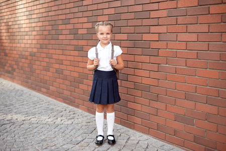 Photo for Full-length of a little smiling girl in school uniform posing against a school entrance background - Royalty Free Image