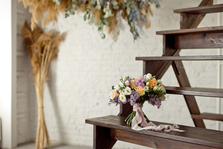 Foto de Wedding bouquet of pink roses with a lilac on a blurred background on a wooden staircase. - Imagen libre de derechos