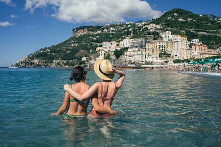 Foto per Two happy girlfriends making fun on the coast of tropical sea - Immagine Royalty Free