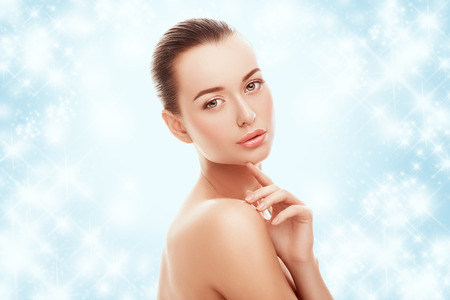 Photo pour Beautiful young girl touching her face on a blue background and snow. Plastic surgery, facelift and rejuvenation concept. Fashion, holiday, cosmetology, people concept. Skincare on winter time. - image libre de droit