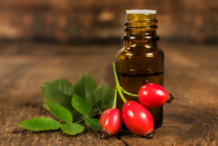 bottle of essential oil of rose hips on wooden background