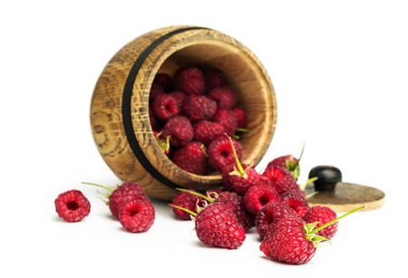 ripe raspberry in a wooden barrel isolated on white