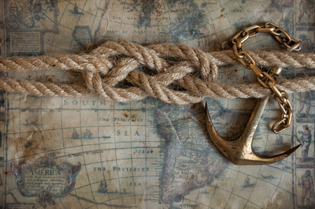 Sailor knot and brass anchor lie on the background of old maps