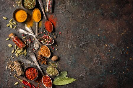 Photo for Top view of mix bright spices in vintage silver spoons, bowls and vials as ingredient for healthy food on brown grunge background with copy space - Royalty Free Image