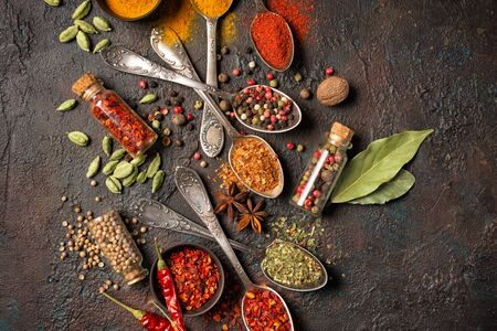 Photo for Top view of mix bright spices in vintage silver spoons, bowls and vials as ingredient for healthy food on brown grunge background - Royalty Free Image