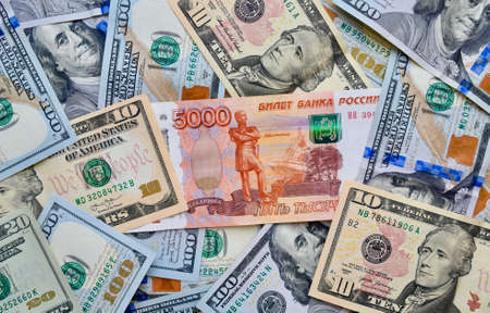 Photo pour Russian national currency on top of US dollar banknote, top view of mixed rouble banknotes. Russian and American paper money. Rubles and US dollars exchange rate. - image libre de droit