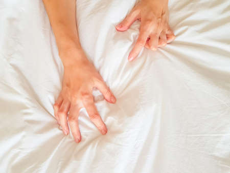 Foto de Close up sexy woman hand pulling and squeezing white sheets in ecstasy in bed. Orgasm on white bed. Sex and erotic concept. High quality photo - Imagen libre de derechos
