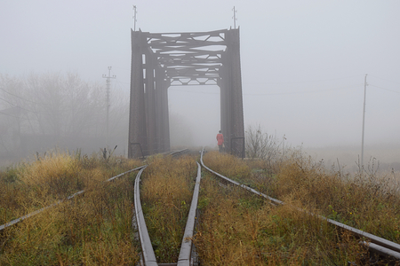 Railway bridge in the fog and a lonely passer-by on the bridge.