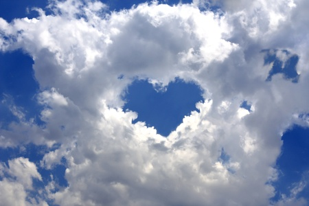 Gray fluffy clouds in the blue sky. In the center of the clouds break in the shape of a heart