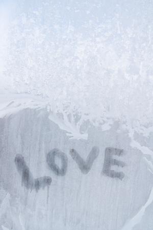 Love inscription on the frozen window in winter patterns in winter