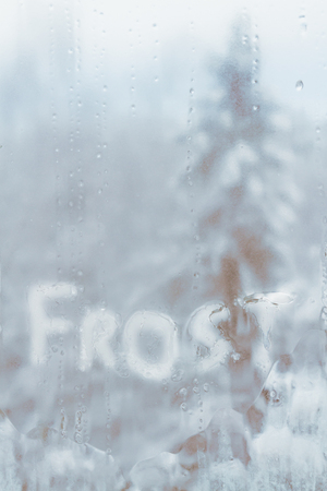 Inscription frost on frozen cold of the winter window