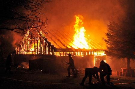 House in fire at night. Firefighters fighting with fire.