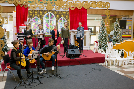 VILNIUS, LITHUANIA - DECEMBER 19, 2015: Christmas traditional concert of classical music of young talented guitarists and vocalists  in Panorama  market. Each New Year concerts look thousands of people