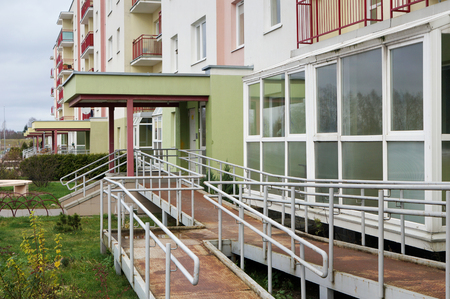A rusty metal ramp for wheelchairs in a  mass production city house where people with disabilities live