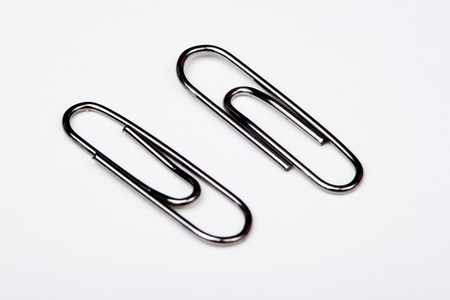 Muchos clips de metal sobre fondo blanco - A lot of metal paperclips on a white background