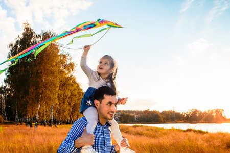 Photo for happy father with a little daughter, having fun in nature, in the rays of the sunset. - Royalty Free Image