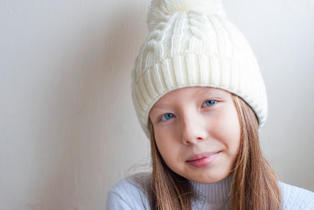 Cute little girl in white knitted hat, mittens and sweater smiling and looking in camera on bright background