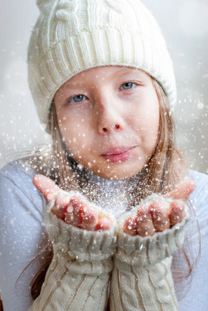 Happy beautiful young girl in white  knitted hat blowing snowflakes from her hands in a winter day