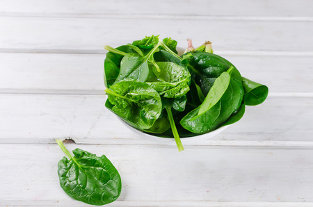 Photo for raw green spinach leaves in white bowl on wooden old rustic white table, copy space - Royalty Free Image