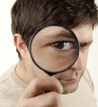 Image of young man looking through a magnifying glass