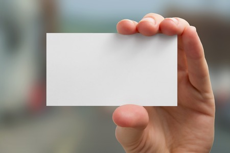 Photo pour Hand holding white business card on blurred background. - image libre de droit