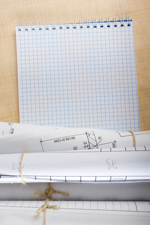 Architectural blueprints and blueprint rolls on white background