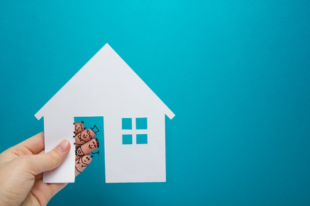 Hand with funny fingers holds white paper house figure on blue background. Real Estate Concept. Ecological building. Copy space top view