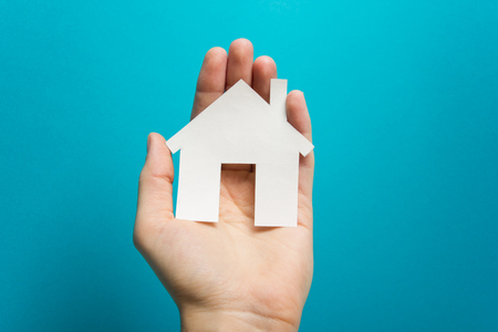 Hand holding white paper house figure on blue background. Real Estate Concept. Ecological building. Copy space top view