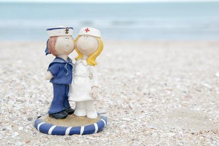 old cute sailor and nurse doll on beach